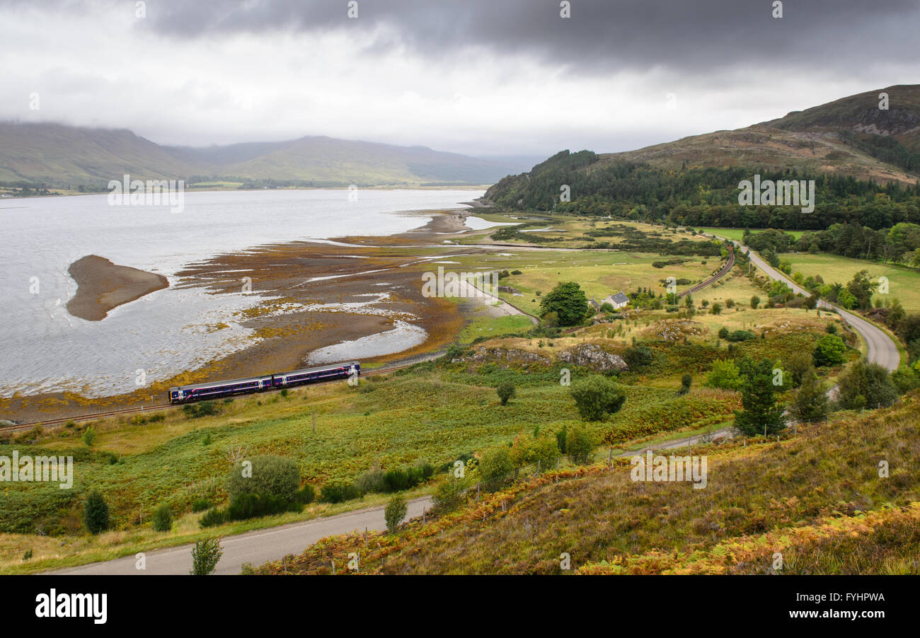 A Scotrail Class158 diesel multiple unit passenger train on the Kyle of Lochalsh railway line at Attadale, beside - Stock Image