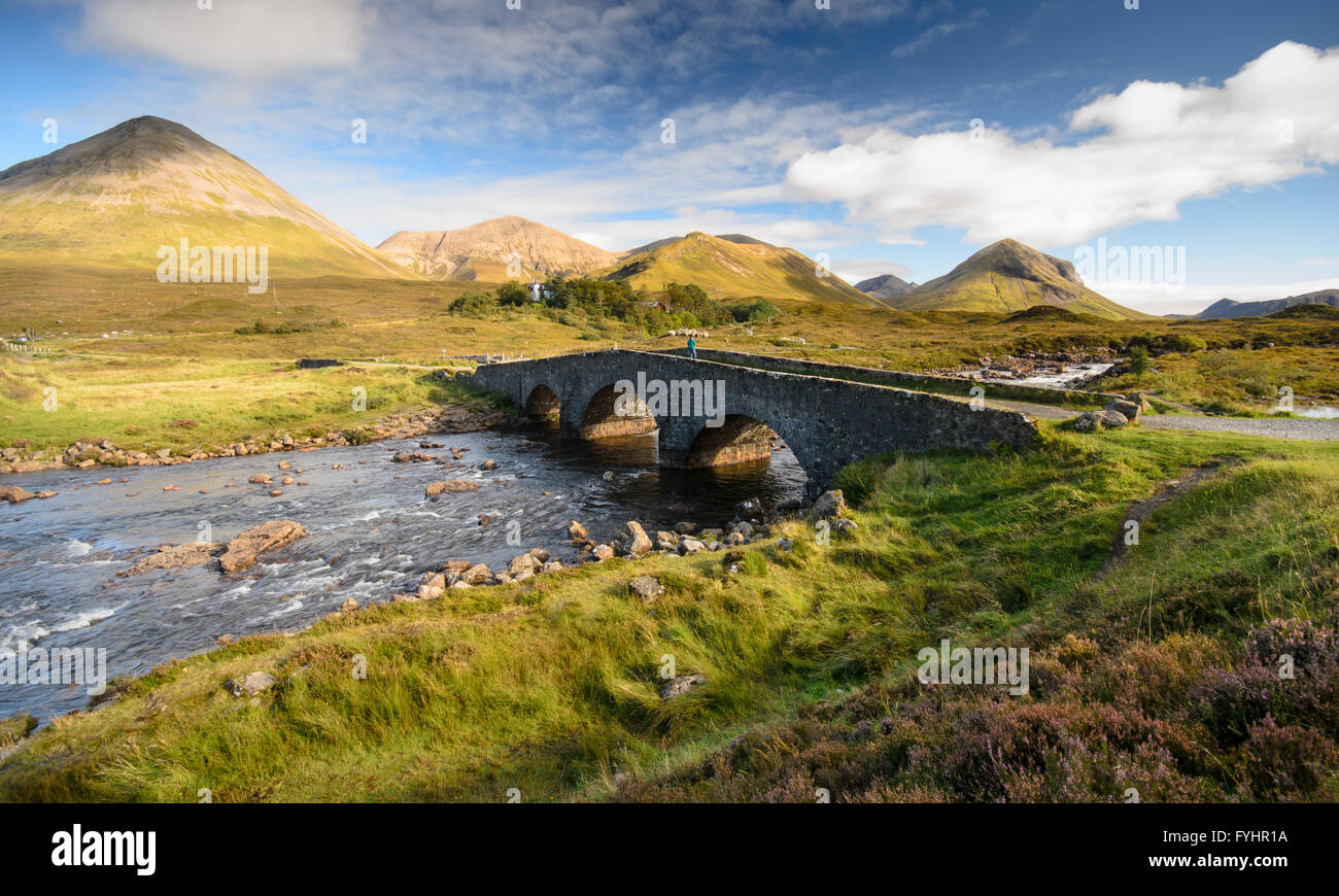 Old stone arch bridge over a mountain river at Sligachan on the Isle of Skye in the Highlands of Scotland. Stock Photo