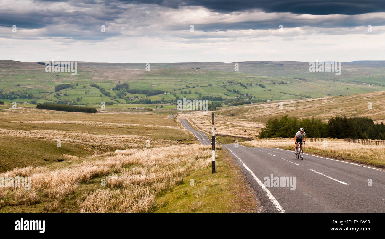 A road cyclist climbs Chapel Fell, the hill dividing Weardale and Teesdale in England's remote North Pennines. - Stock Image