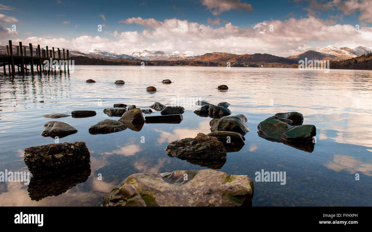 The rocky shore of Lake Windermere in the English Lake District, with a pier and mountains providing the backdrop. - Stock Image