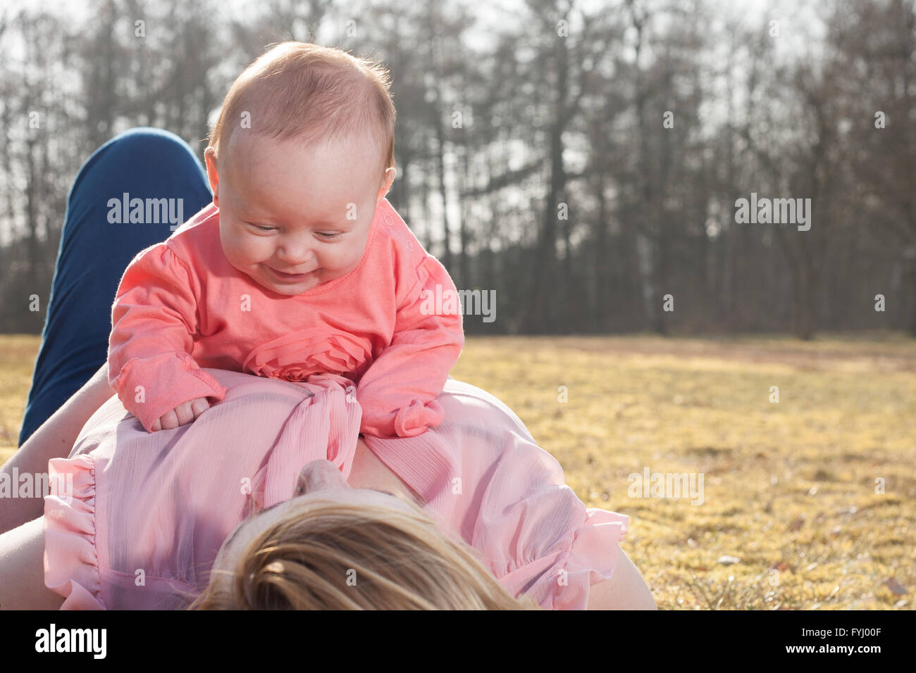 Baby is having fun on moms belly - Stock Image
