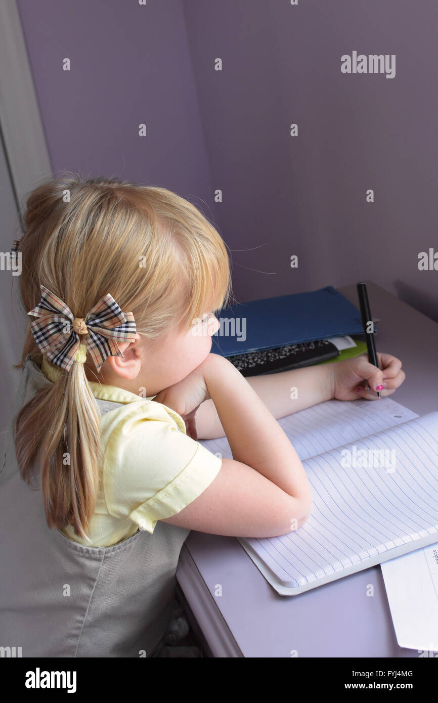 young girl child doing homework - Stock Image