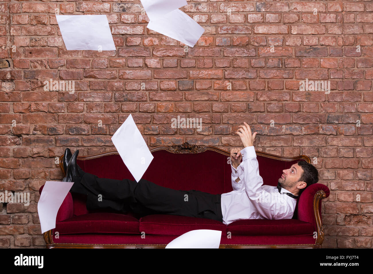 Businessman lying on a settee with flying papers - Stock Image