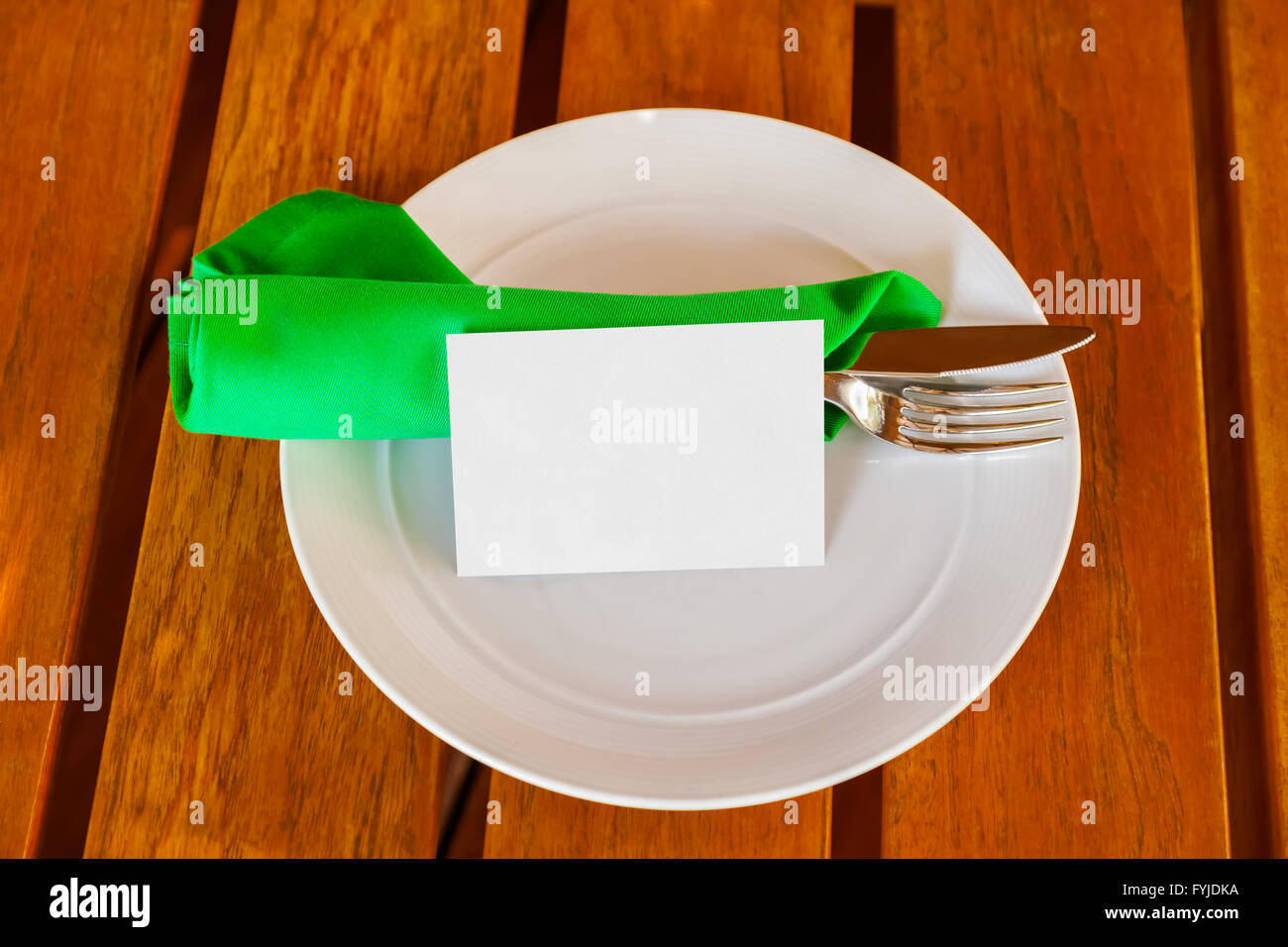 Dishware and blank paper card on table in restaurant Stock Photo