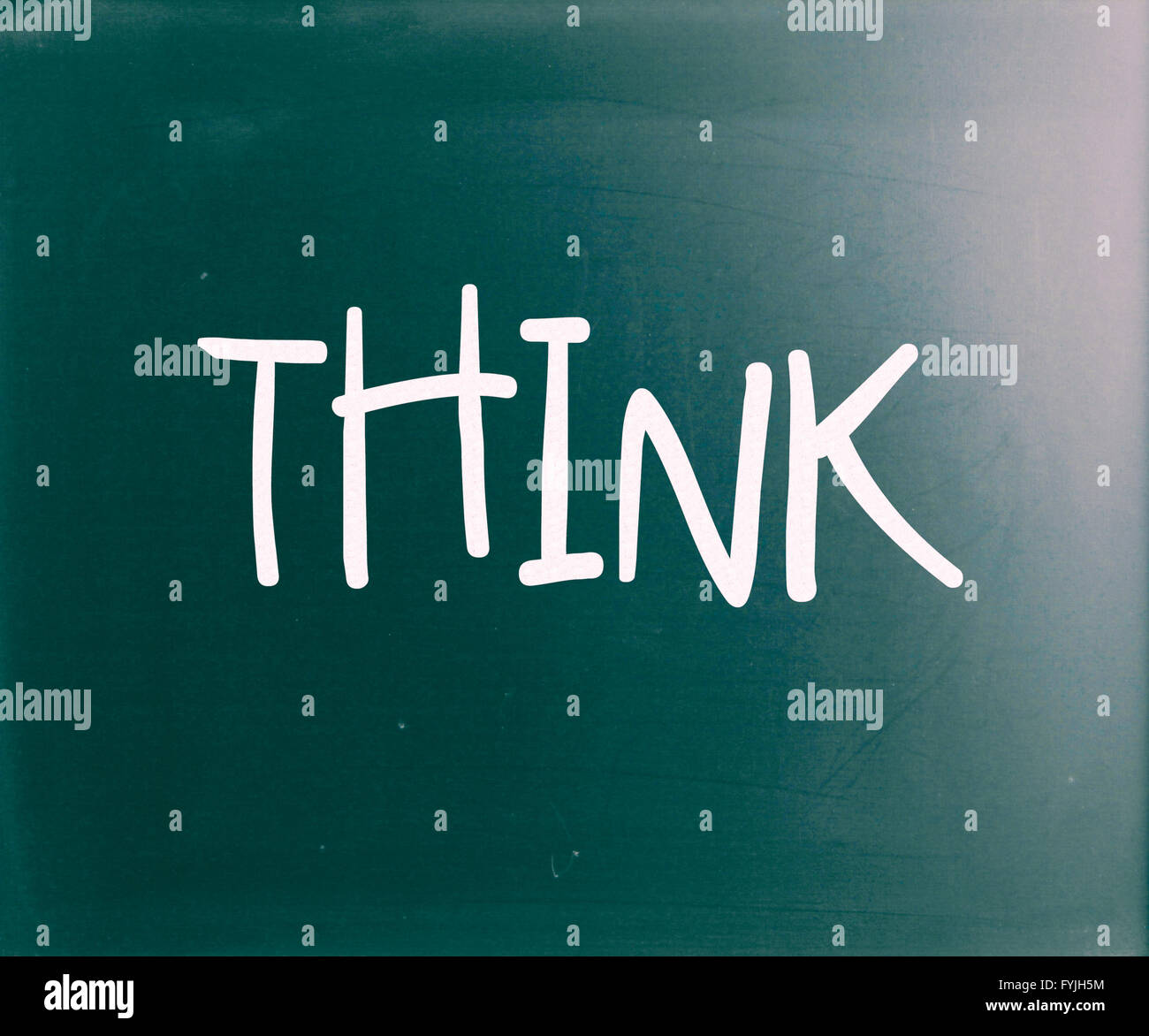 The word Think handwritten with white chalk on a blackboard - Stock Image