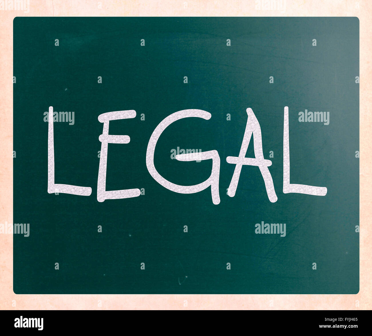 The word Legal handwritten with white chalk on a blackboard - Stock Image