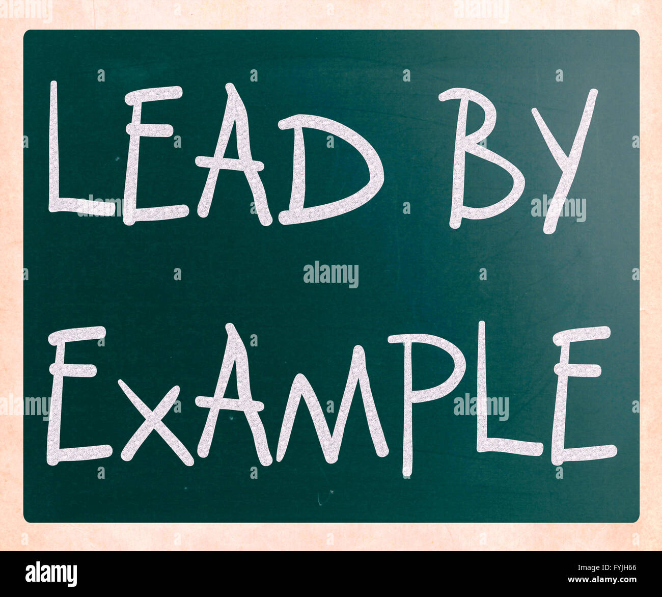 Lead by example handwritten with white chalk on a blackboard - Stock Image