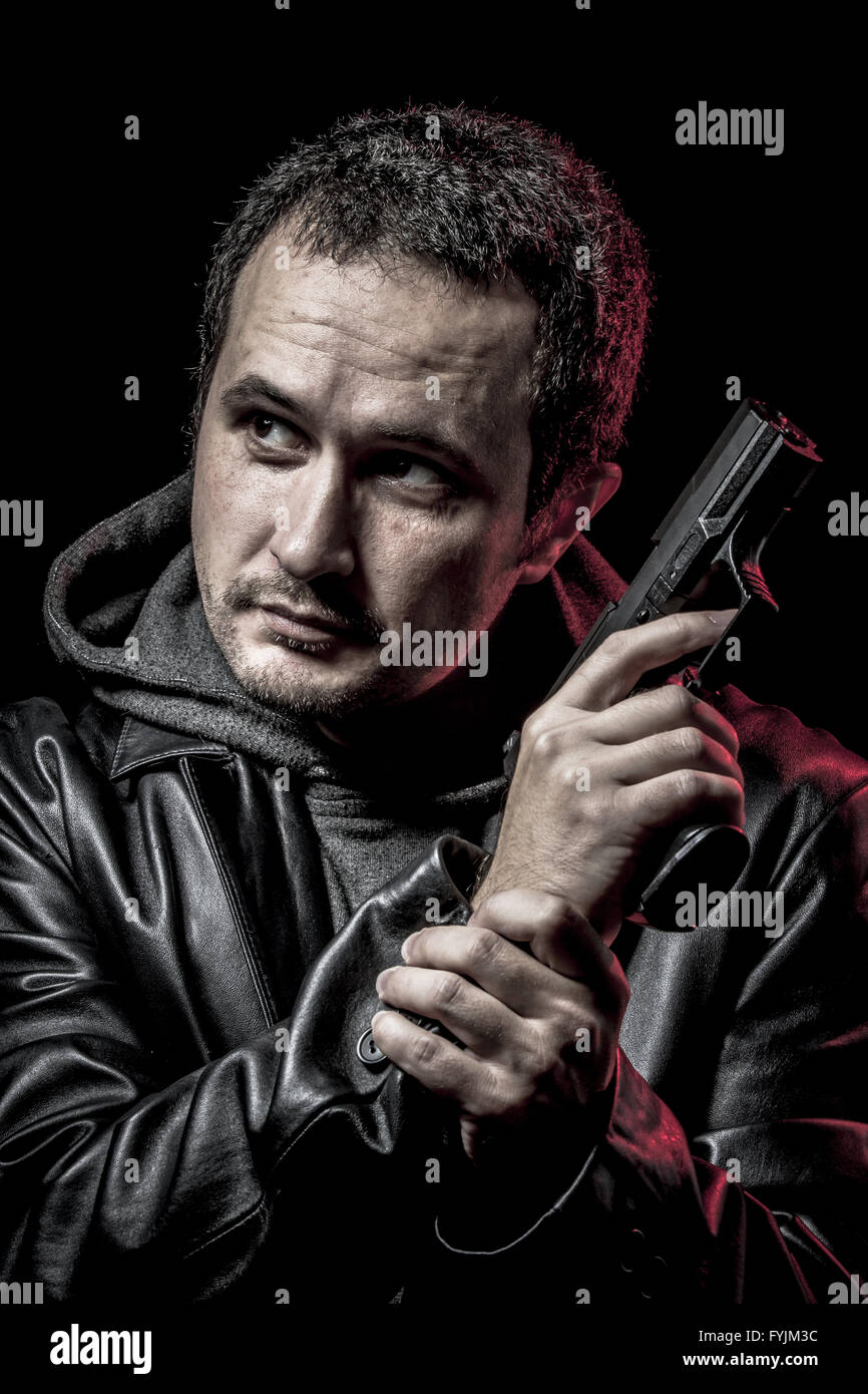 thief, armed man with black leather jacket, dangerous - Stock Image
