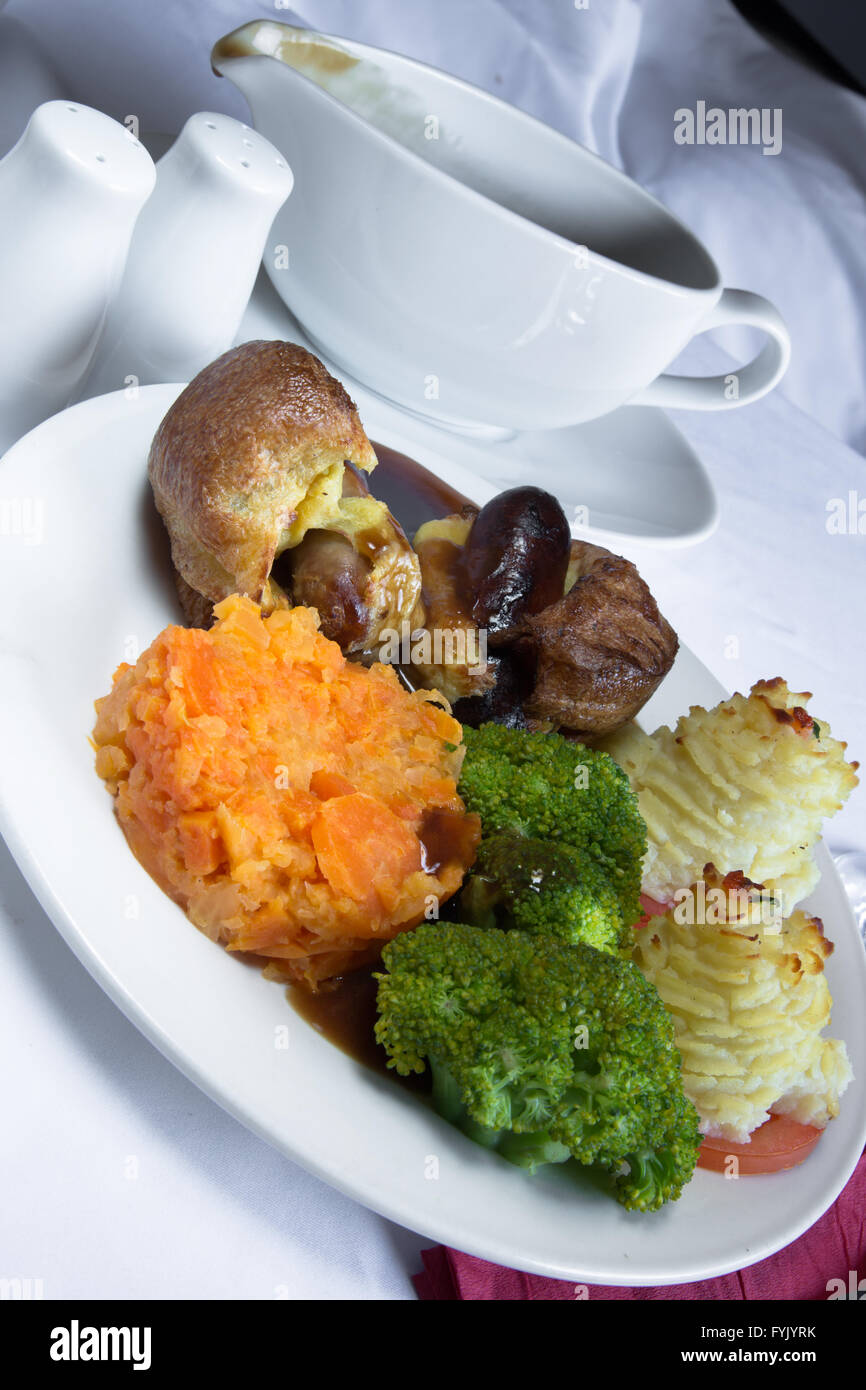 A serving of English style Toad in the Hole with Duchess Potato, Broccoli, Carrot and a rich brown gravy. - Stock Image