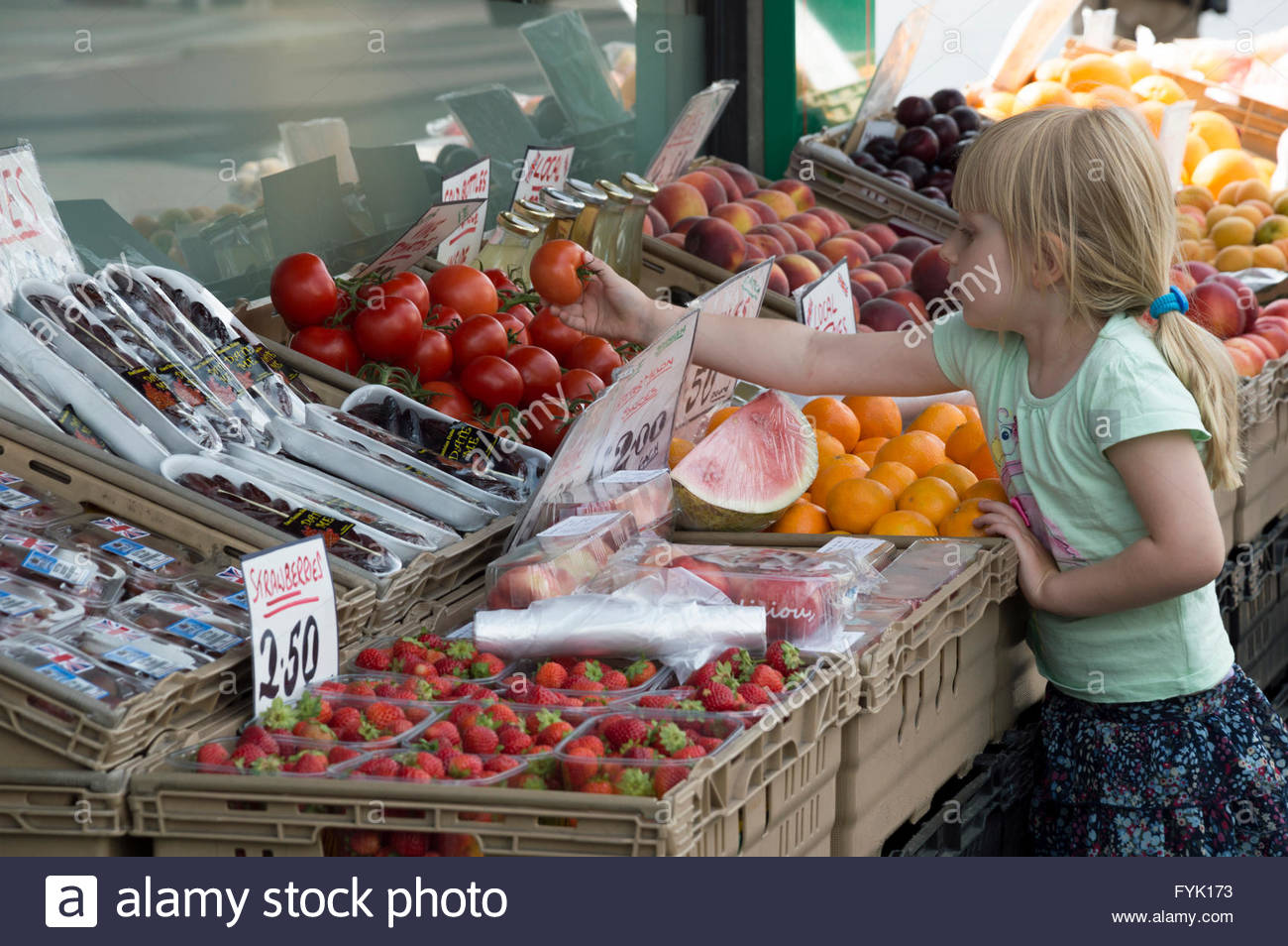 A little girl picks a tomato from the display outside a shop, Broadstairs, Kent - Stock Image