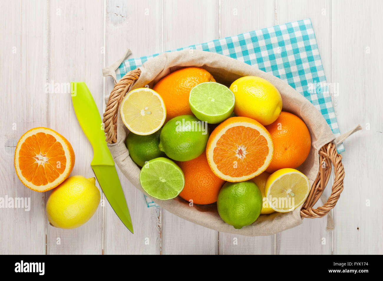 Citrus fruits in basket. Oranges, limes and lemons. Over white wood table background - Stock Image