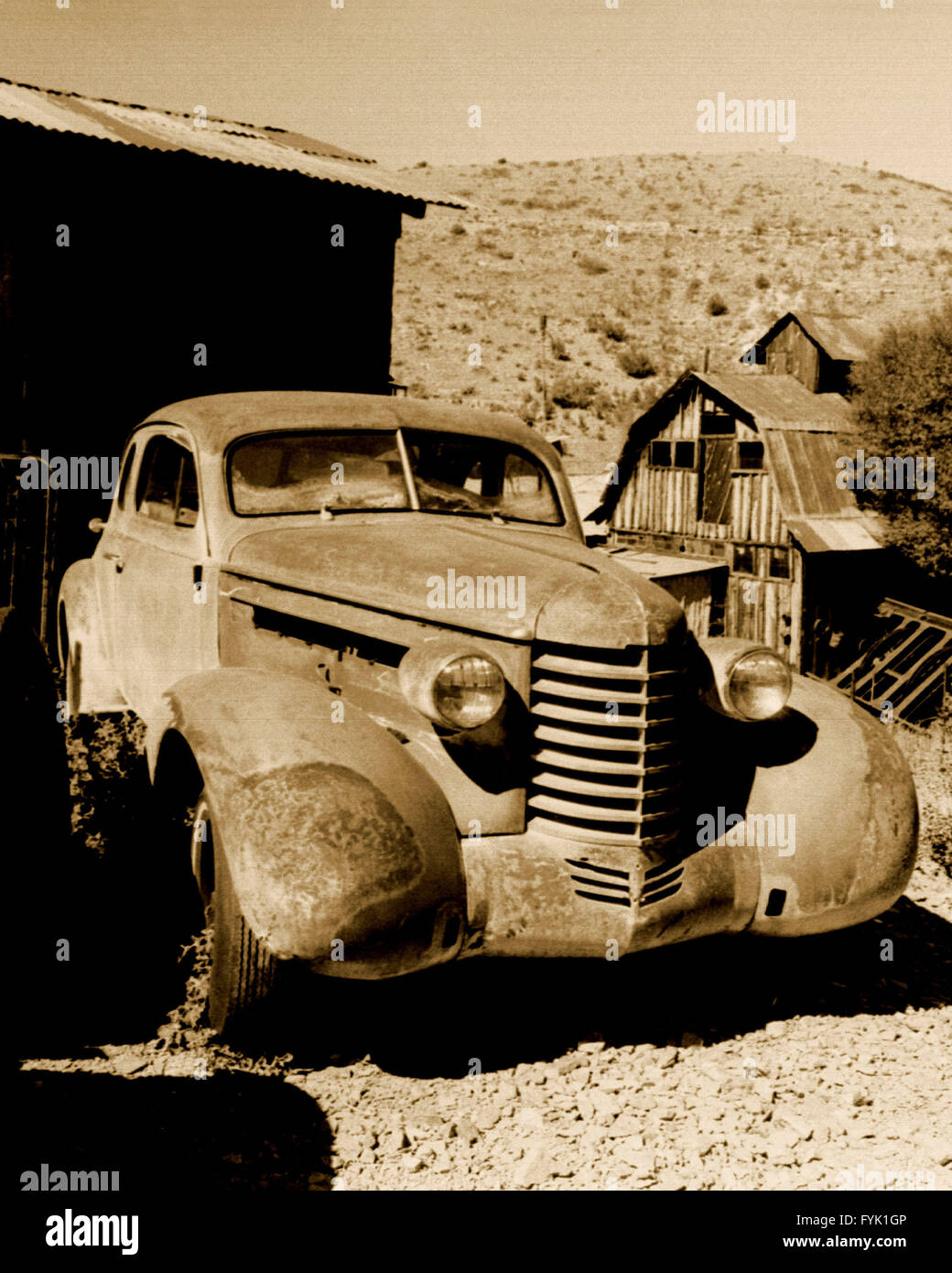 An evil looking mobster type vintage vehicle rusting and rotting in the Arizona sun. - Stock Image