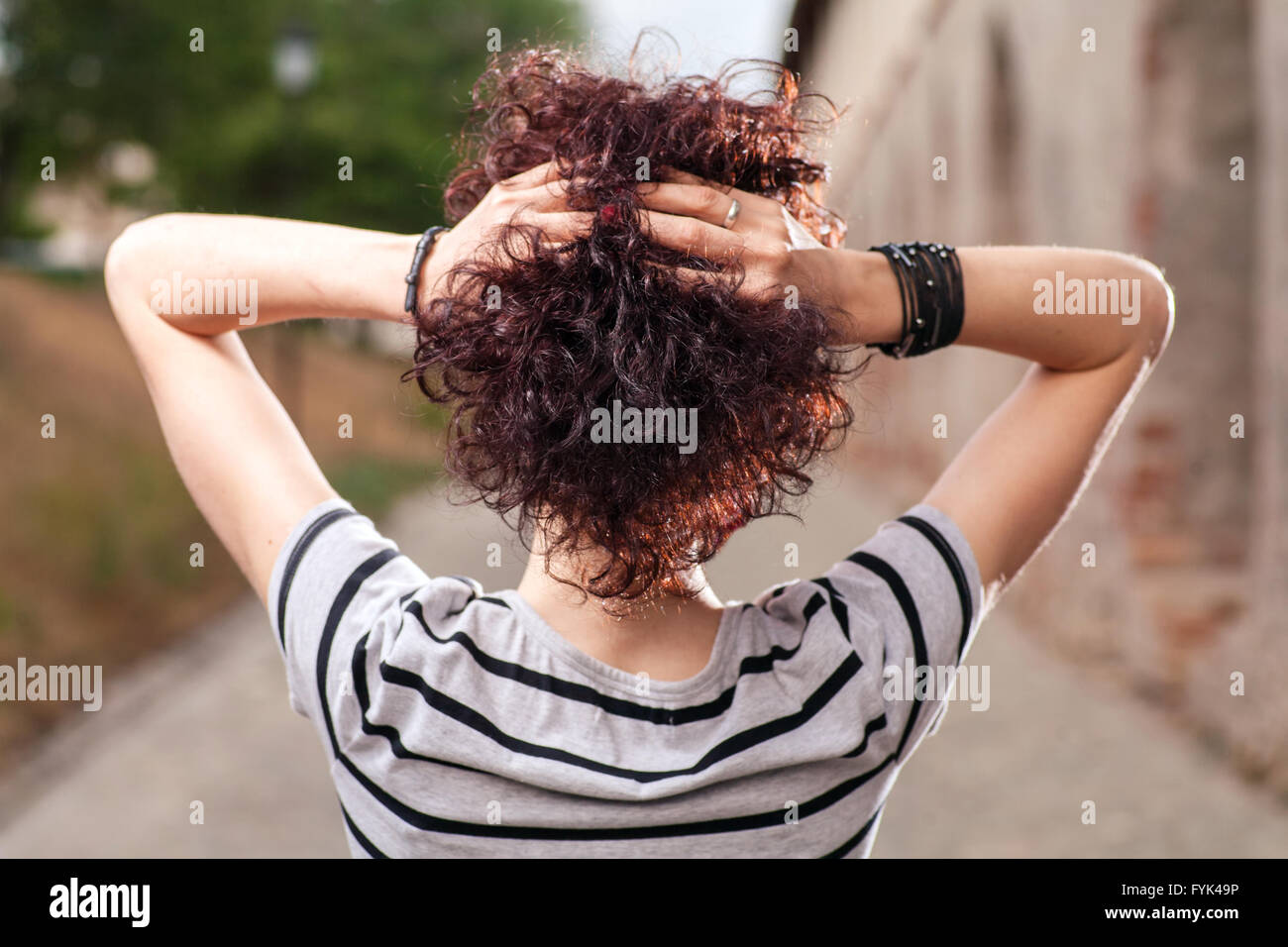 Spacious rear view of a girl with red curly hair - Stock Image