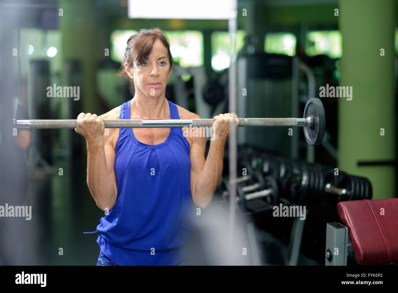 Retired woman working out with weight handle bar in front of mirror at the gym - Stock Image