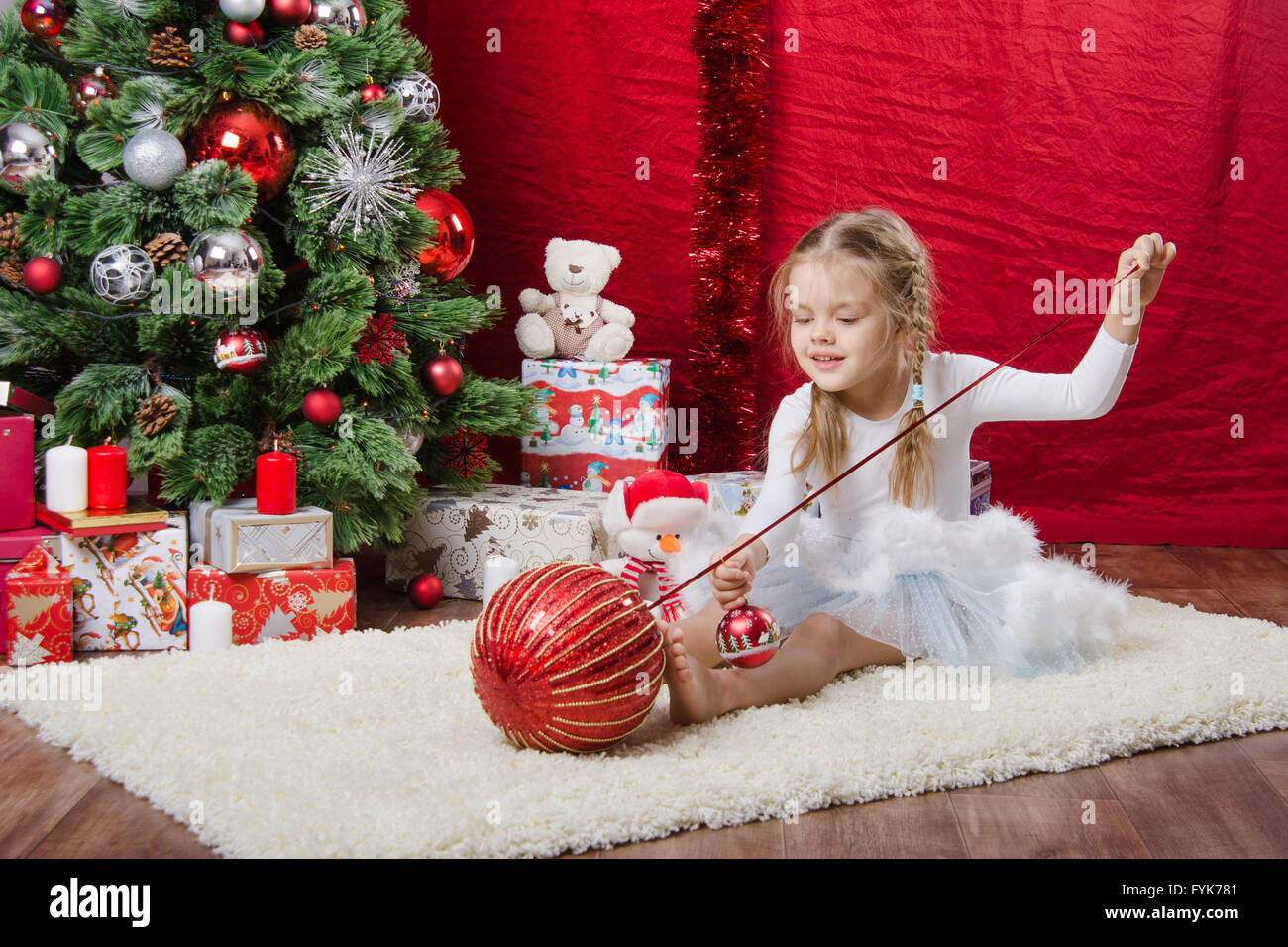 Five-year girl with balloons near Christmas tree - Stock Image