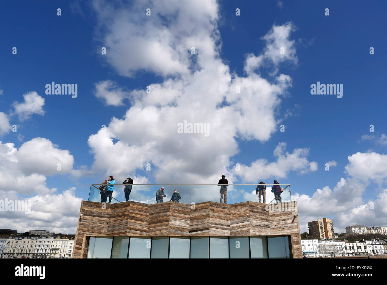 Hastings, UK. 27th Apr, 2016. People look out from a viewing platform on the newly reopened Hastings Pier in Hastings, - Stock Image