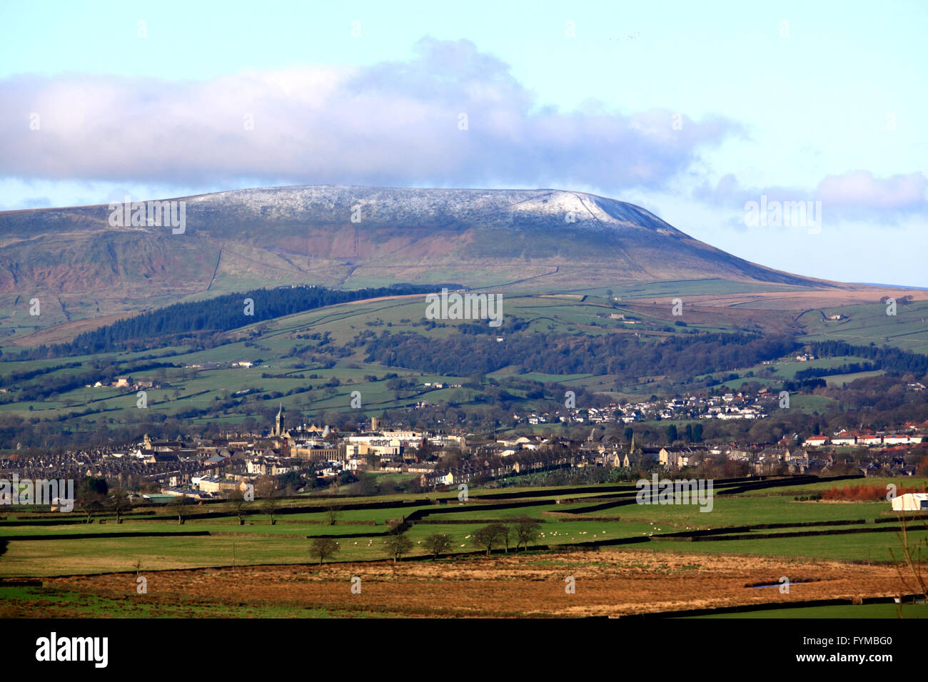 The 'Big End' of Pendle Hill with a dusting of snow looks down on the town of Colne, Lancashire. - Stock Image