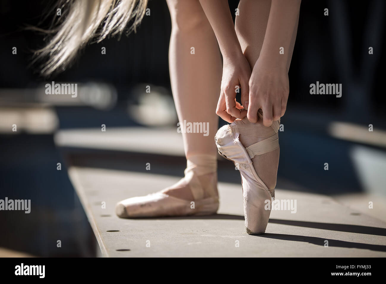 Dancer tying pointe shoes - Stock Image