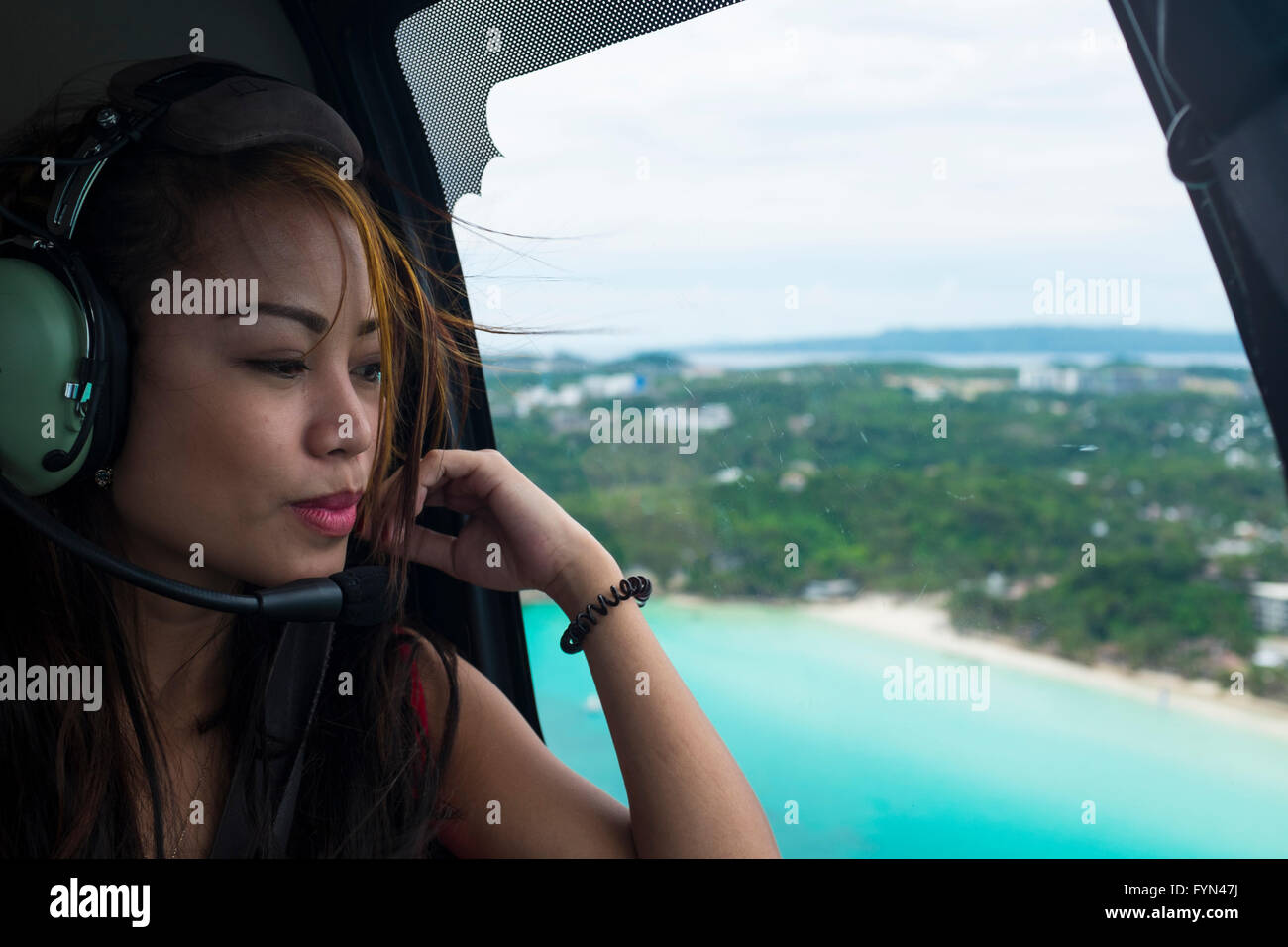 Beautiful Asian girl in a helicopter over Boracay, Philippines - Stock Image