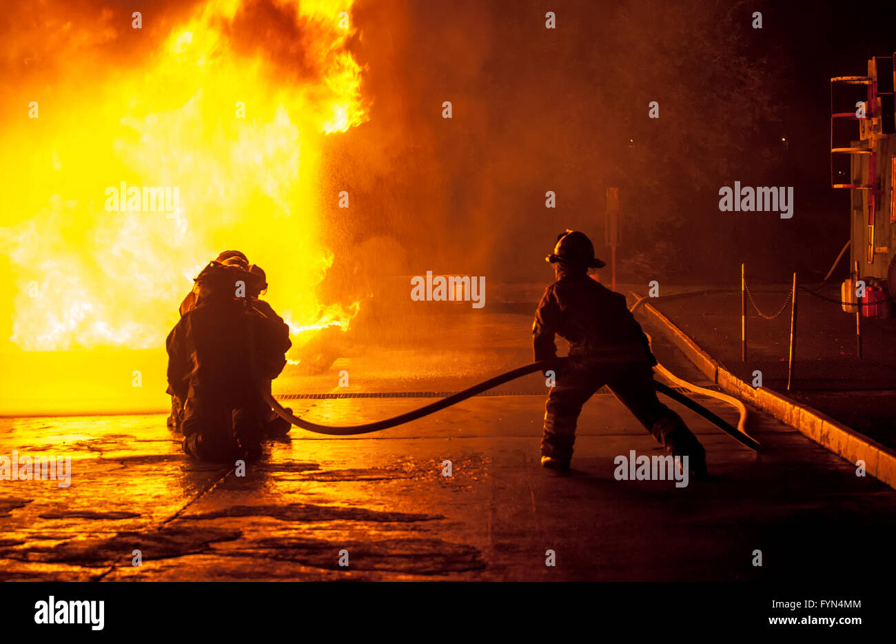 Firefighters controlling water hose - Stock Image