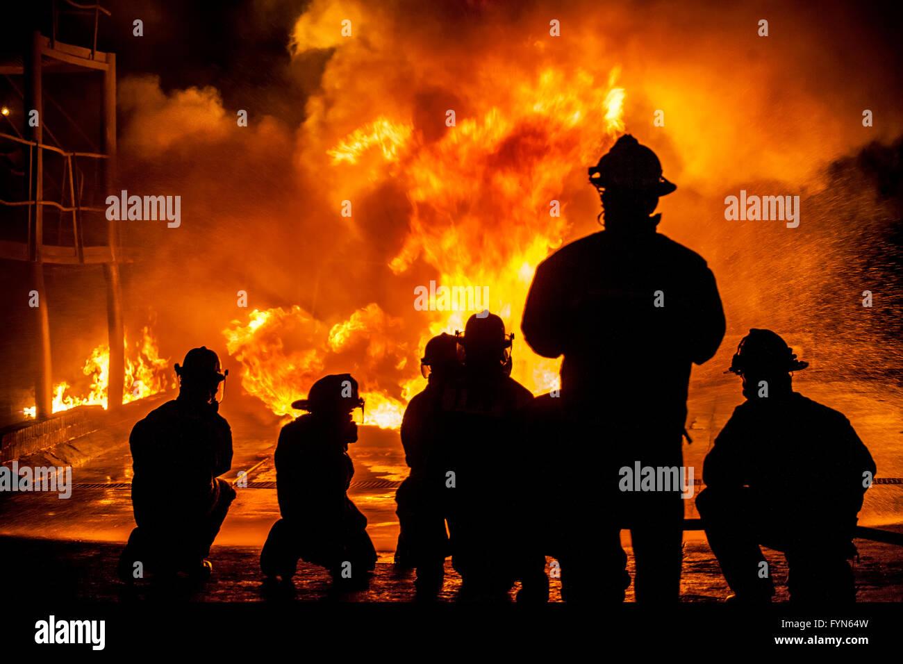 Firefighters fighting burning blaze - Stock Image