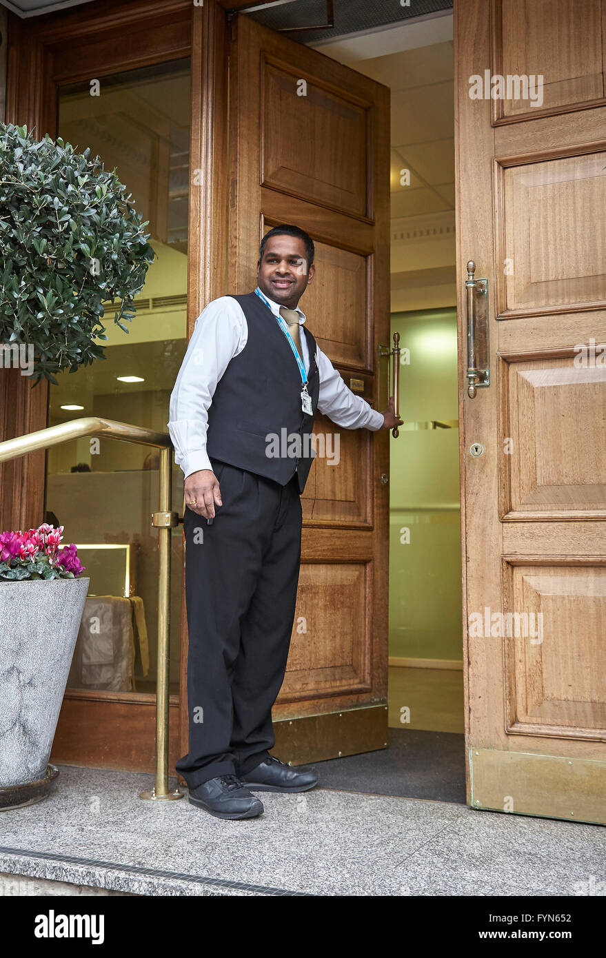 A hotel bellboy or Porter opening the front door of a hotel for a guest in the UK. - Stock Image