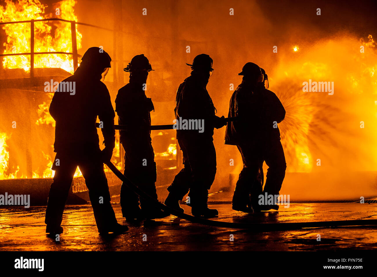 Firefighters hosing down fire - Stock Image