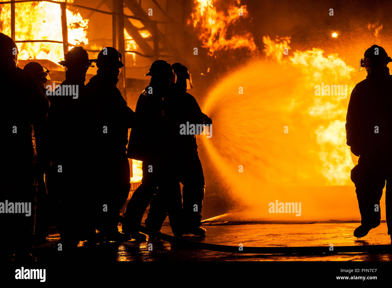 Firefighters putting out burning structure with water - Stock Image