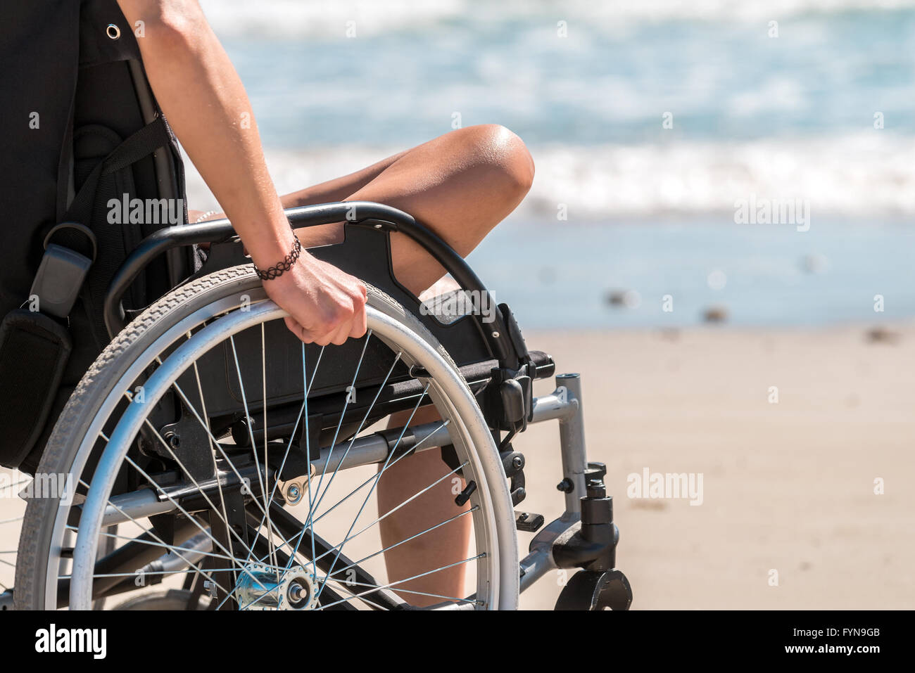 Disabled woman in the wheelchair at the beach - Stock Image