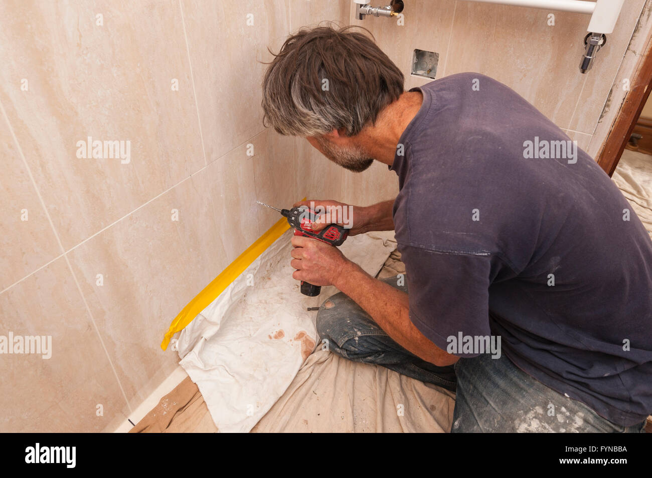A Builder Drilling A Hole Through Ceramic Tiles In The Uk Stock