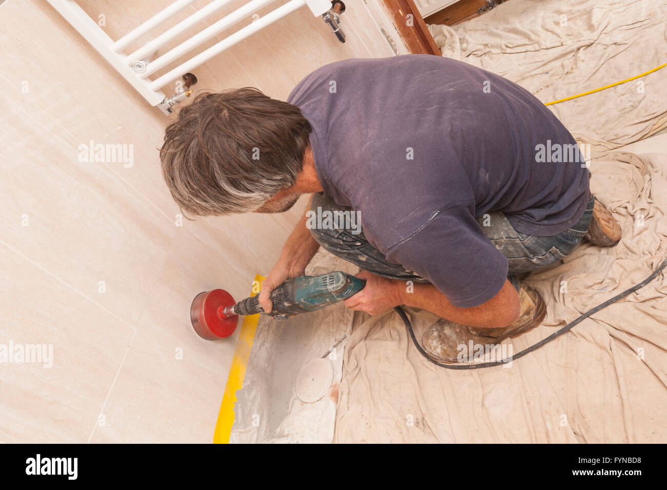 A builder drilling a hole through ceramic tiles for a 4 inch soil ...