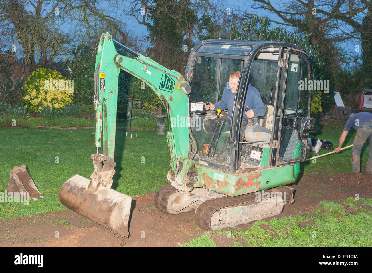 A man in his mini digger filling in a trench in the Uk - Stock Image