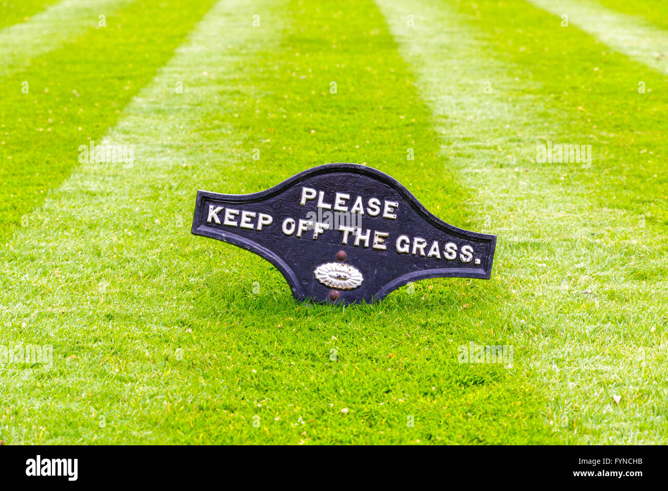 A beautiful green garden lawn that has just been mowed a sign of Please Keep Off The Grass - Stock Image