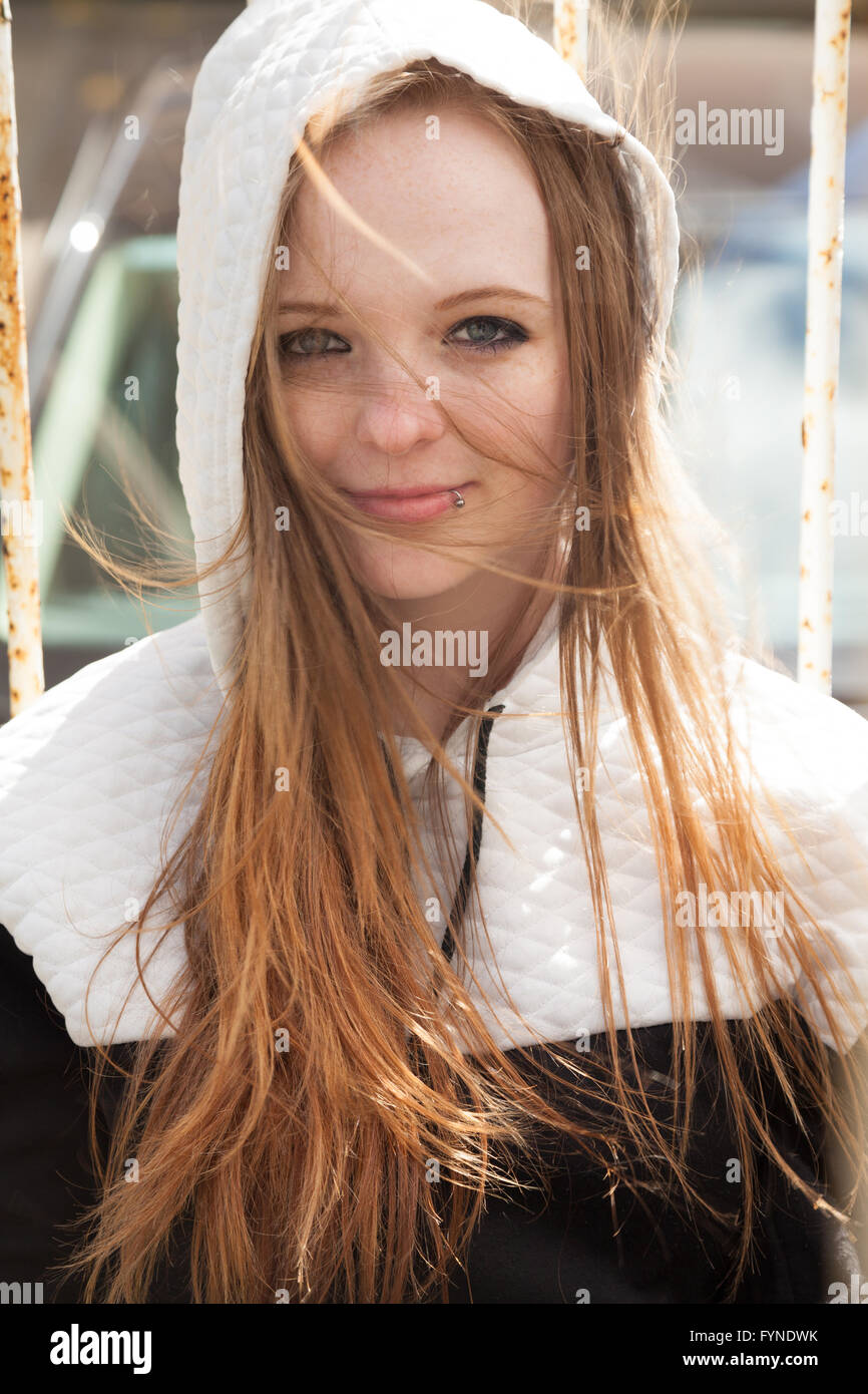 A red headed woman with long wind blown messy hair. - Stock Image