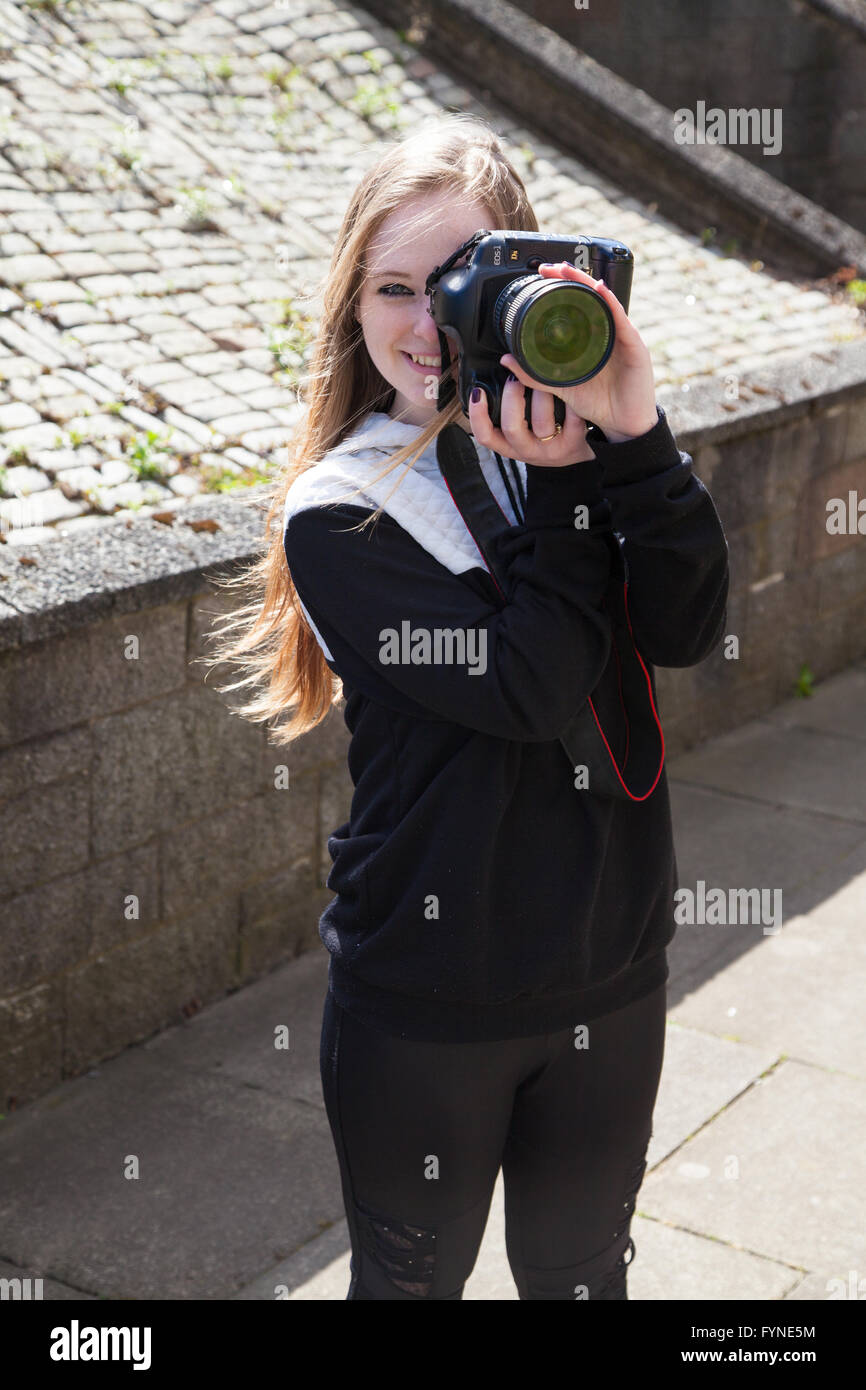A female photographer pointing her digital camera towards the viewer. - Stock Image