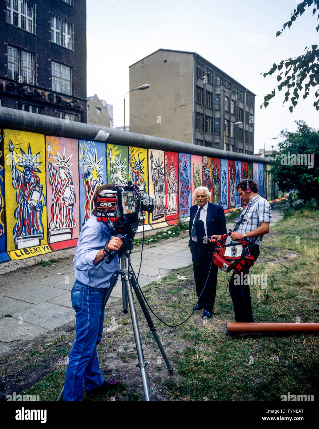 August 1986, CBS TV crew conducting an interview in front of Berlin Wall decorated with Statue of Liberty frescos, - Stock Image