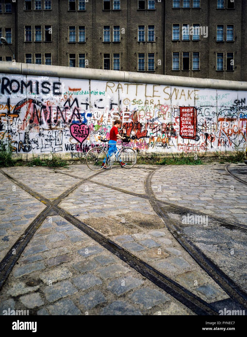 August 1986, Berlin Wall graffitis, tram track ending into wall, cyclist, East Berlin building, West Berlin side, - Stock Image