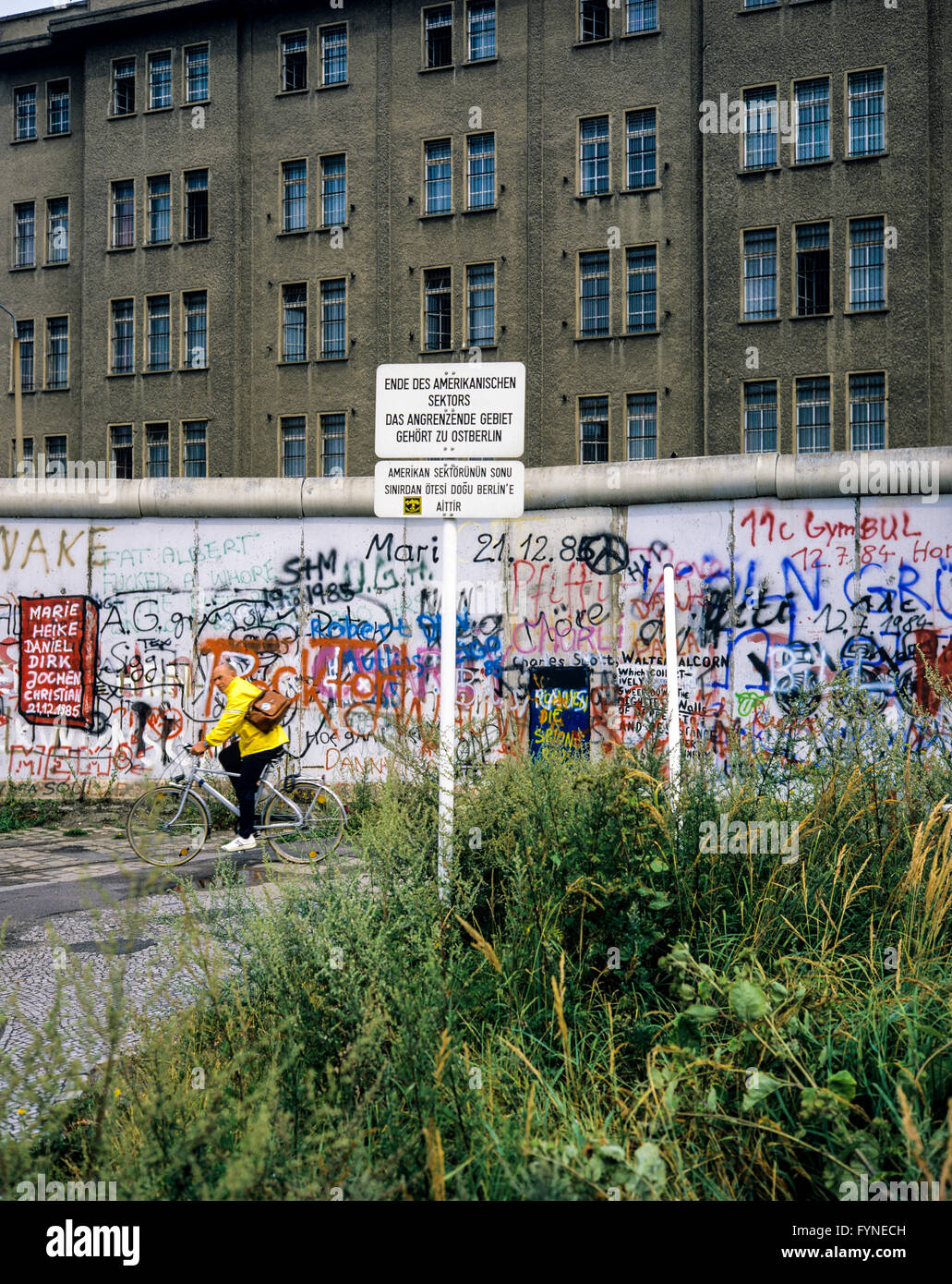 August 1986, Berlin Wall graffitis, warning sign for end of American sector, cyclist, East Berlin building, West - Stock Image