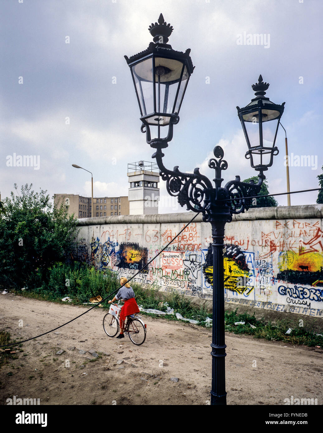 August 1986, Berlin Wall graffitis, street lamp, cyclist, East Berlin watchtower, Zimmerstrasse street, Kreuzberg, - Stock Image