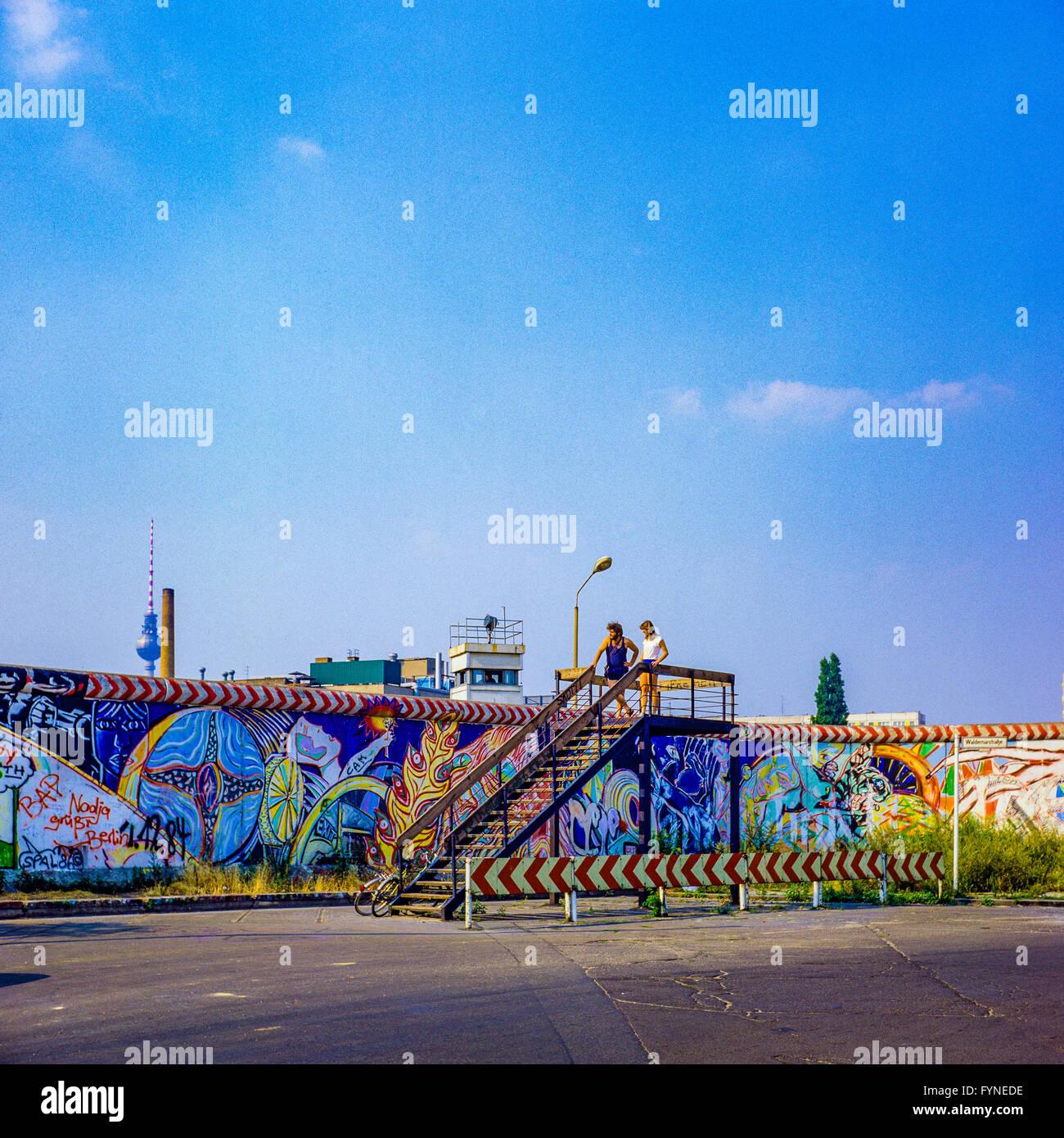 August 1986, Berlin Wall graffitis, young couple on observation platform, East Berlin watchtower, Kreuzberg, West - Stock Image