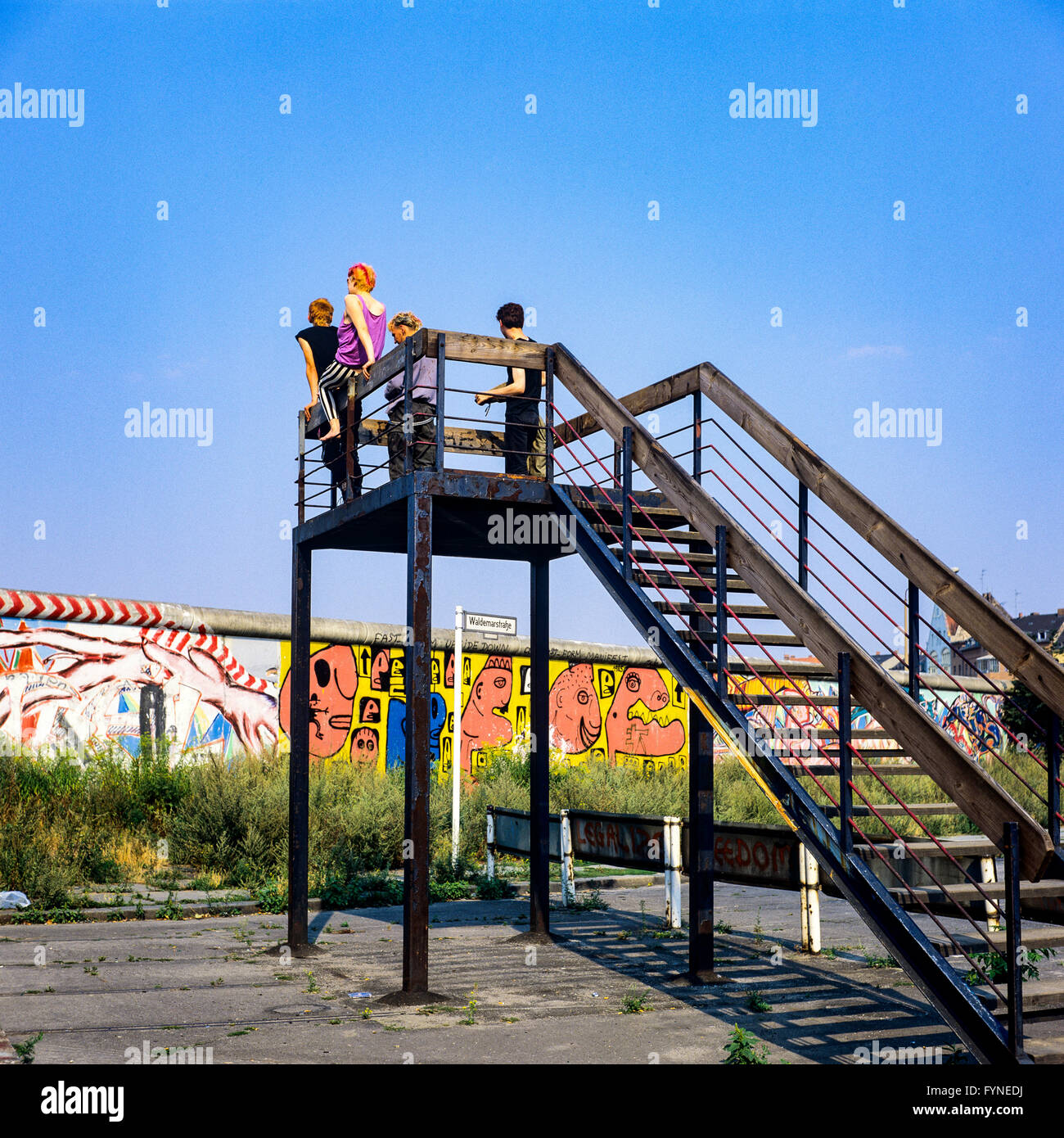 August 1986, Berlin Wall graffitis, four young people on observation platform looking over the Wall, Kreuzberg, - Stock Image