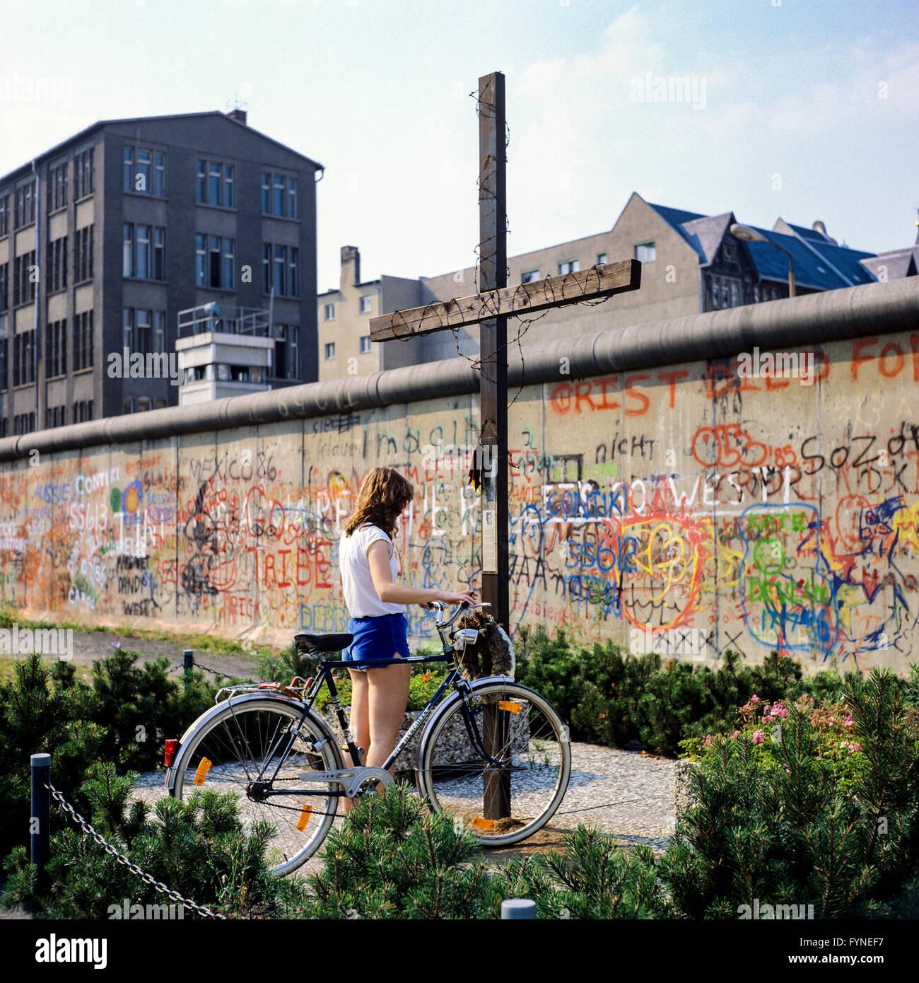August 1986, young woman with bike, Peter Fechter memorial, graffitis on Berlin Wall, Zimmerstrasse street, Kreuzberg, Stock Photo