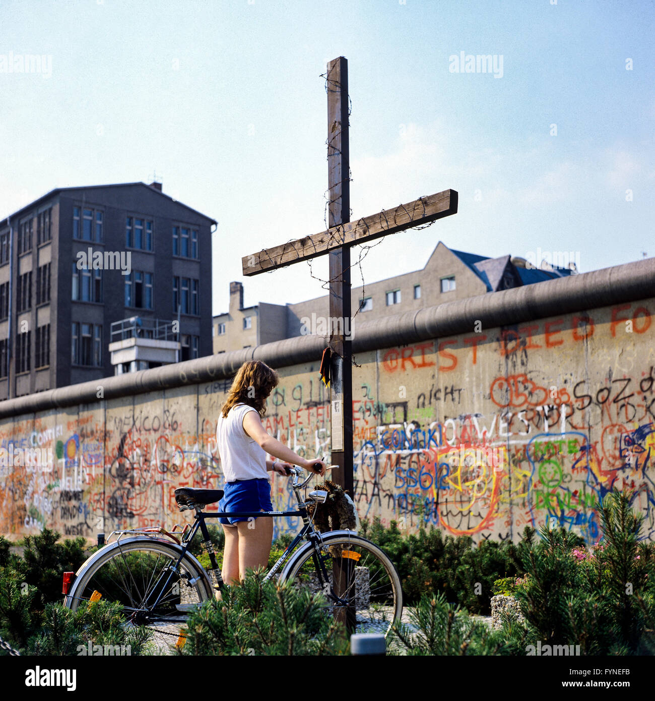 August 1986, young woman with bike, Peter Fechter memorial, graffitis on Berlin Wall, Zimmerstrasse street, Kreuzberg, - Stock Image