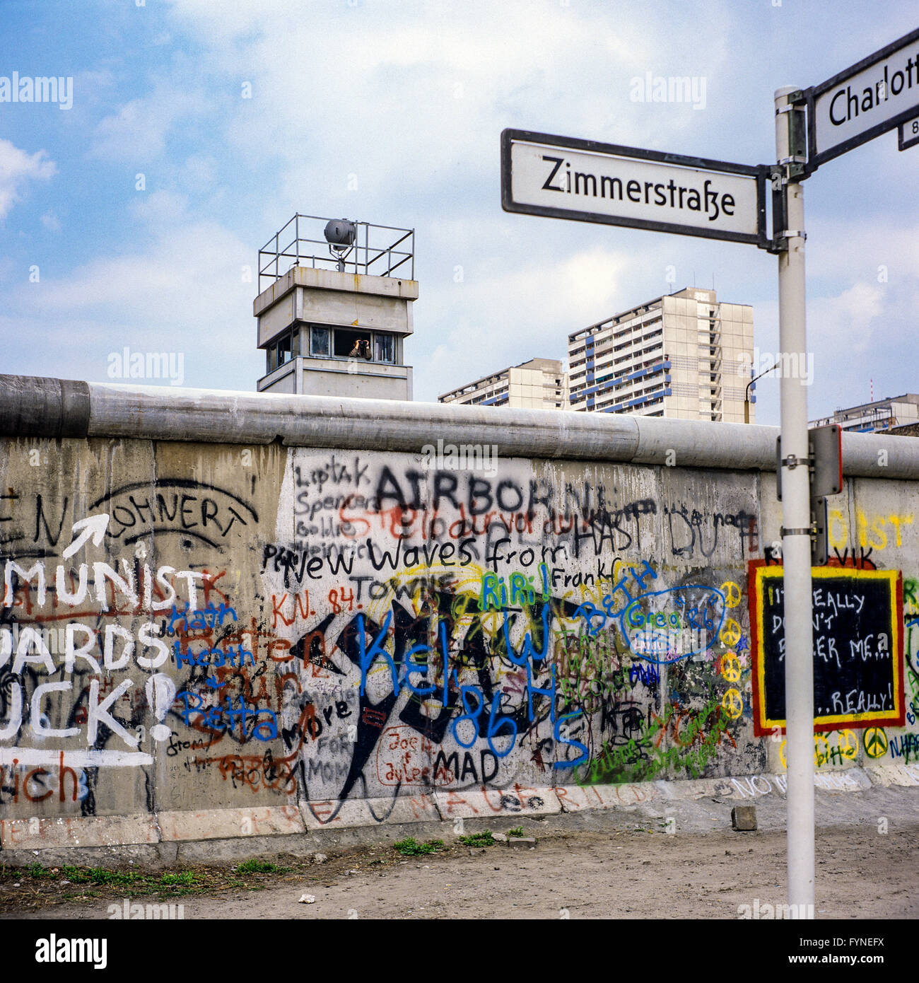 August 1986, graffitis on the Berlin Wall and East Berlin watchtower, Zimmerstrasse street sign, Kreuzberg, West - Stock Image