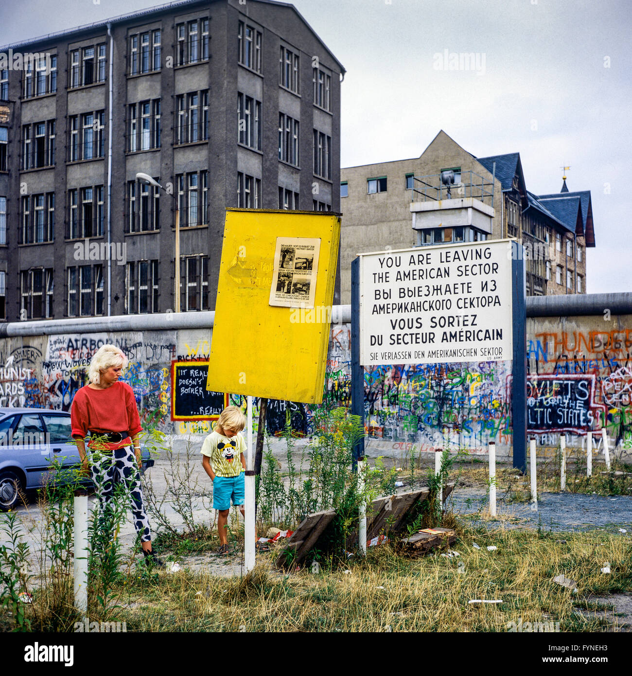 August 1986, woman and boy, leaving American sector warning sign, Berlin Wall graffitis, Zimmerstrasse street, West Stock Photo