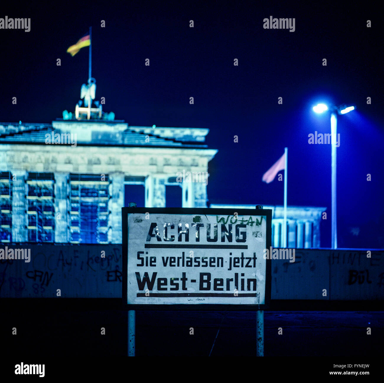 August 1986, leaving West Berlin warning sign front of the Berlin Wall, Brandenburg Gate at night in East Berlin, - Stock Image