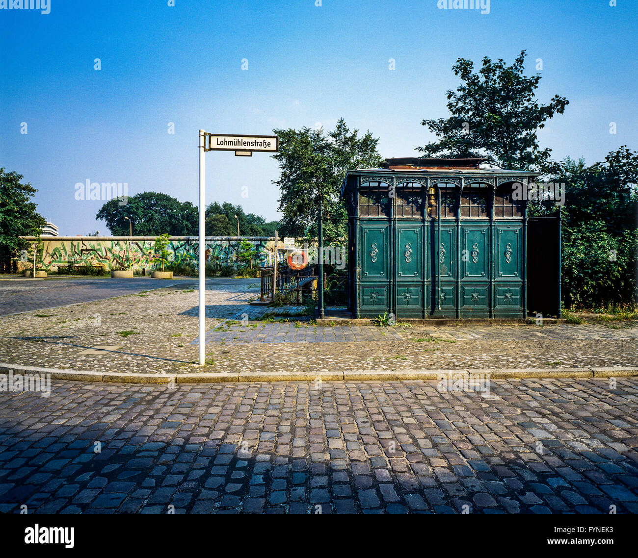 August 1986, ancient public toilet 1899, Berlin Wall graffitis, Lohmühlenstrasse street sign, Treptow, West - Stock Image
