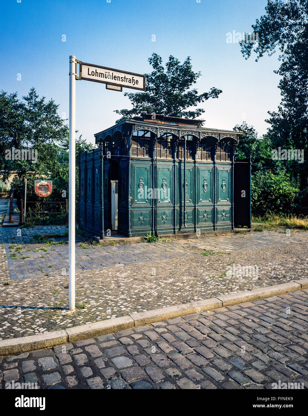 August 1986, ancient public toilet 1899, Lohmühlenstrasse street sign, Treptow, West Berlin side, Germany, - Stock Image
