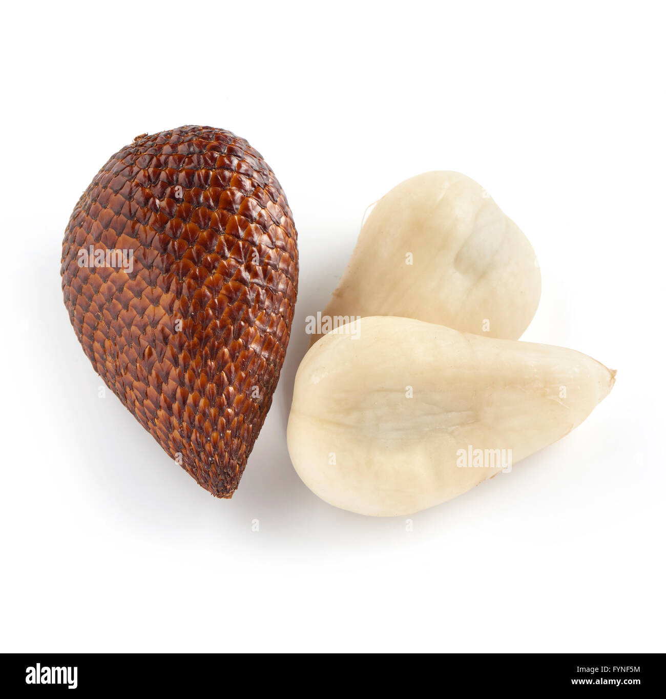 Close Up Still Life of One Unpeeled Exotic Salak Palm Fruit with Brown Scaly Skin, and Two Halves of Flesh from - Stock Image