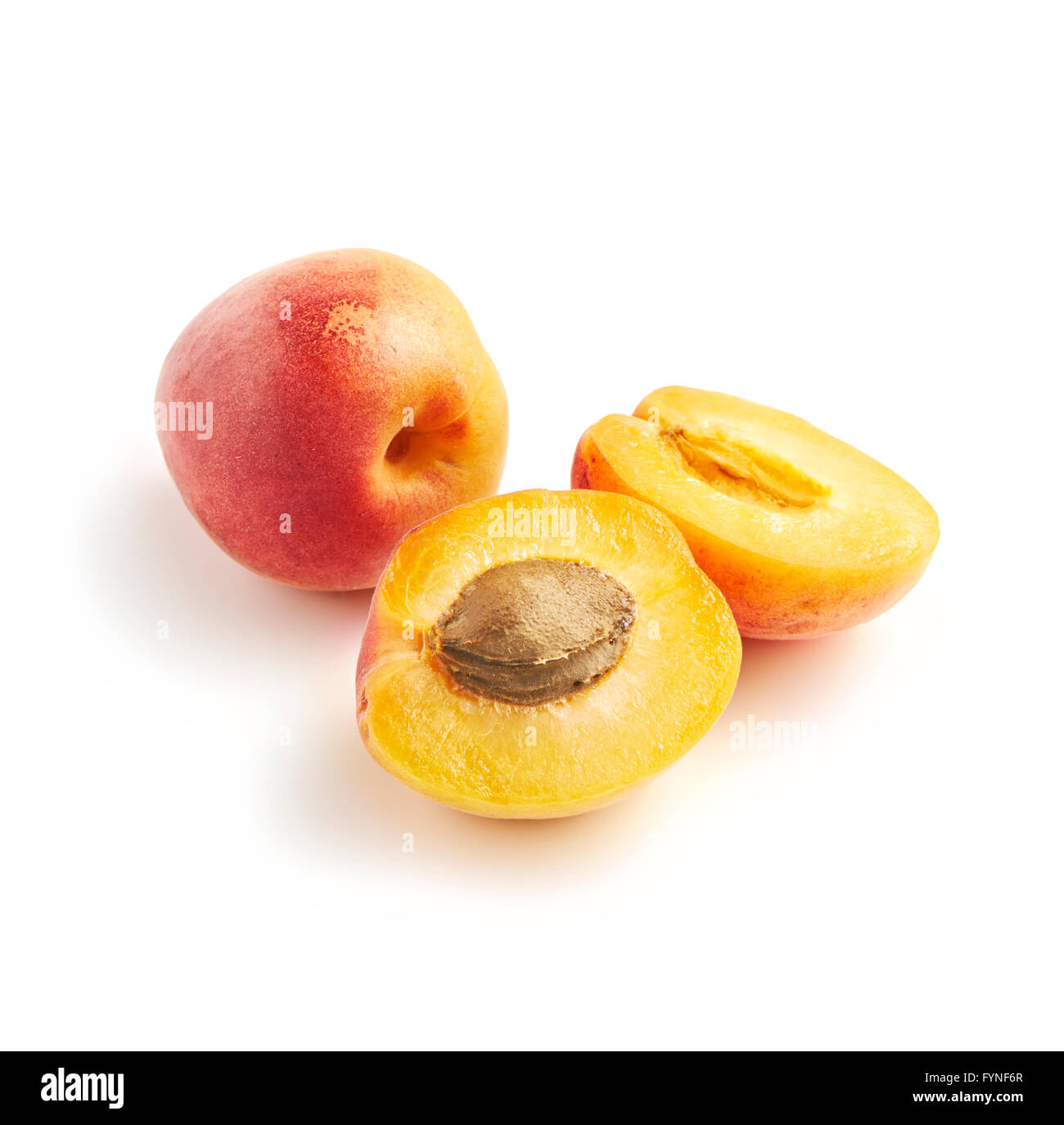 Halved and whole sweet juicy fresh apricots on a white background displaying the stone or pip Stock Photo